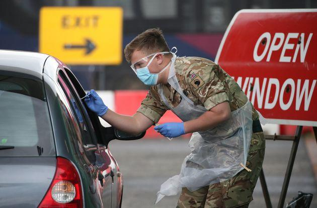 A soldier from 2 Scots Royal Regiment of Scotland take a test sample at a Covid-19 testing centre at Glasgow airport.