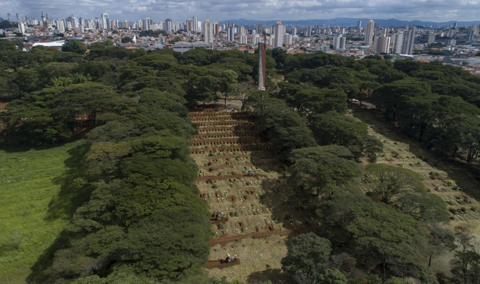 Workers use small bulldozers to dig more graves amid the COVID-19 pandemic at the Vila Formosa cemetery in Sao Paulo, Brazil, Wednesday, April 7, 2021. The city of Sao Paulo started on Wednesday the digging of 600 additional graves every day in its municipal cemeteries. (AP Photo/Andre Penner)