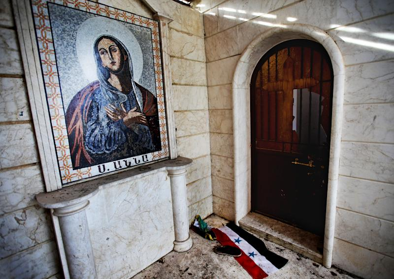 In this Thursday, Feb. 21, 2013 photo, a Syrian flag is seen on the ground next to the mosaic of Santa Ana, at the Santa Ana Armenian Orthodox church, which was use as a base by the Syrian army forces, at the Christian village of Yacobiyeh, in Idlib province, Syria. Yacobiyeh and its neighbors, Judeida and Quniya, are some of the first Christian villages to be taken by the rebel Syrian Army. The rebels stormed these hilltop villages in late January, after the army used it as a base to shell nearby rebel-controlled areas. The villages are largely empty due to the fighting, with a few mostly elderly Christians -- including Roman Catholics and Armenian Orthodox _ living among Sunni Muslim refugees who have moved up here from the plains. They still face sporadic artillery bombardment from below.(AP Photo/Hussein Malla)