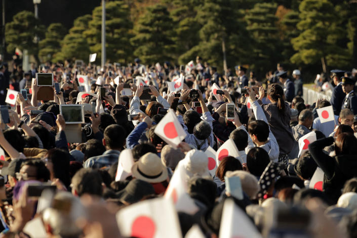 Spectators take pictures as the royal motorcade of Japanese Emperor Naruhito and Empress Masako passes by in Tokyo, Sunday, Nov. 10, 2019. (AP Photo/Jae C. Hong)
