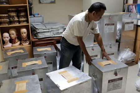 An election official prepares ballot boxes before distributing them to polling stations, in Jakarta