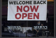 "FILE - In this March 4, 2021, file photo, a sign reading ""Welcome Back Now Open"" is posted on the window of a Morton's Steakhouse restaurant as a man works inside during the coronavirus pandemic in San Francisco. State governments will get a big influx of federal money from the $1.9 trillion COVID-19 relief package that could suddenly enable them to undertake large, expensive projects that have long been on their to-do lists, including high-speed internet for rural areas and drinking water improvements. (AP Photo/Jeff Chiu, File)"
