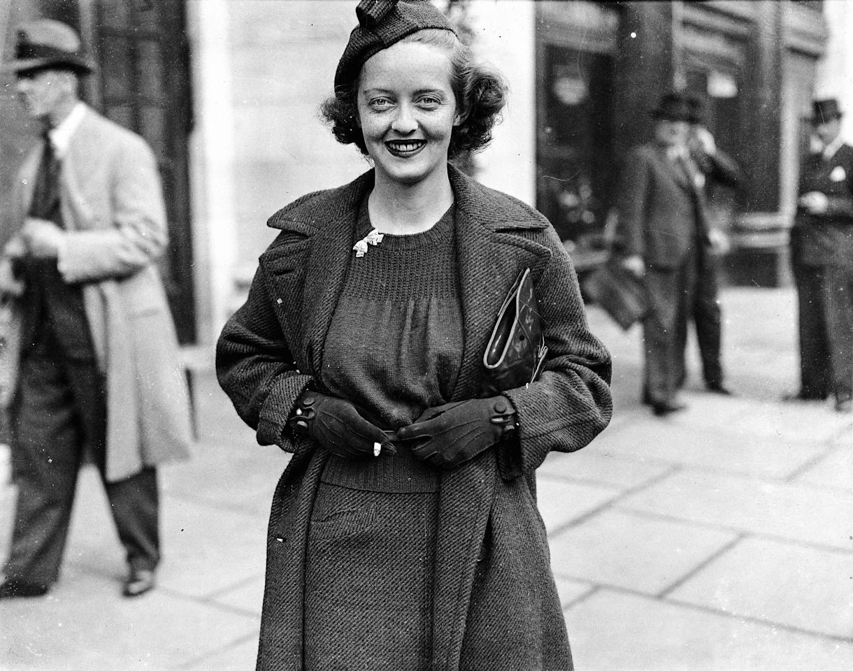 <p>Walking on the streets of London in a tailored dress, gloves, and pillbox hat.</p>