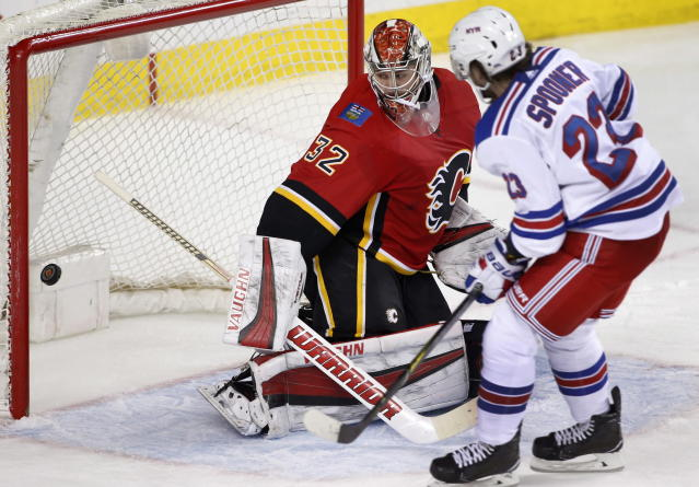 New York Rangers' Ryan Spooner, right, scores against Calgary Flames goalie Jon Gillies during second-period NHL hockey game action in Calgary, Alberta, Friday, March 2, 2018. (Larry MacDougal/The Canadian Press via AP)