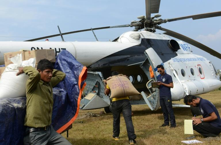 Nepalese villagers load relief materials onto a helicopter at Salyantaar in Dhading District