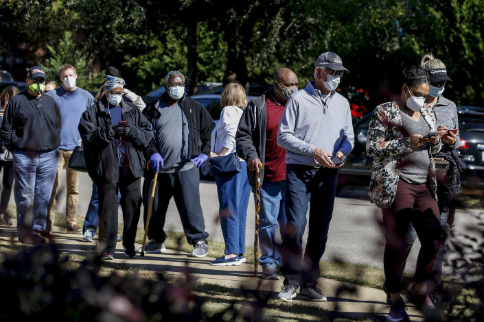 Republican nominee for the Alabama Senate, Tommy Tuberville (third from right), stands in a long line waiting to cast his vote on Tuesday, Nov. 3, 2020, in Auburn, Ala. (AP Photo/Butch Dill)