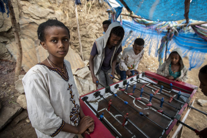 A girl watches while boys and young men play table football on the street, as Ethiopian Orthodox Christians celebrate Easter Sunday, in Gondar, in the Amhara region of Ethiopia Sunday, May 2, 2021. Ethiopia faces a growing crisis of ethnic nationalism that some fear could tear Africa's second most populous country apart, six months after the government launched a military operation in the Tigray region to capture its fugitive leaders. (AP Photo/Ben Curtis)