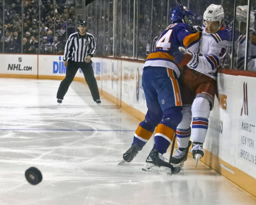 New York Islanders Scott Mayfield (24), left, pins New York Rangers Vladislav Namestnikov (90), right, against the glass during an NHL hockey game Saturday, Jan. 12, 2019, at Barclays Center in New York. (AP Photo/Bebeto Matthews)