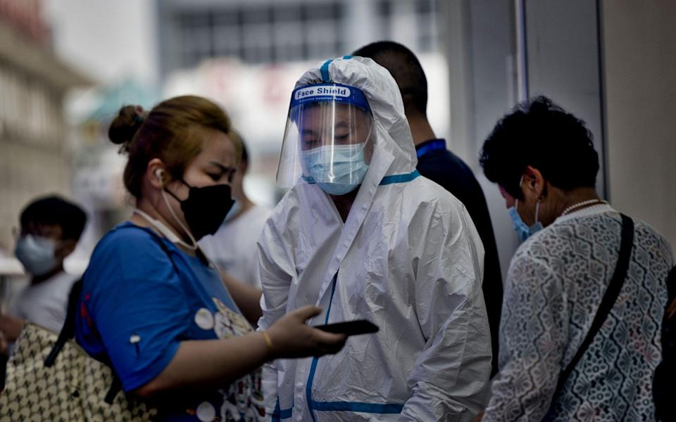 A traveler shows a health code on a smartphone to a medical personnel at the railway station in Shanghai, China, 29 July 2021. China reported 24 new locally transmitted COVID-19 cases, according to the National Health Commission. More than 170 people have been diagnosed with the Delta variant. The main outbreak is in the eastern city of Nanjing, in Jiangsu province. - Shutterstock