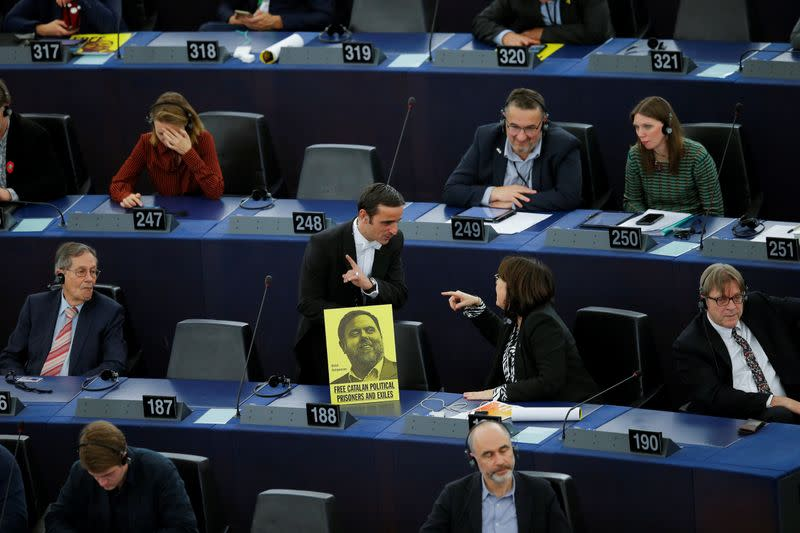 An usher of the parliament removes a banner depicting jailed Catalan leader Oriol Junqueras during a plenary session of the European Parliament in Strasbourg