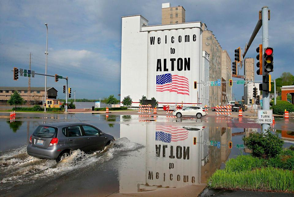 <p>A vehicle drives through Mississippi River flood water in downtown Alton, Il. on Monday, May 6, 2019.</p>