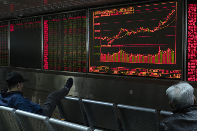 Investors monitor stock prices at a brokerage in Beijing Thursday, Jan. 16, 2020. Share prices are mixed in moderate trading in Asia after the U.S. and China signed a preliminary trade agreement that investors hope will bring better relations between the two biggest economies. (AP Photo/Ng Han Guan)