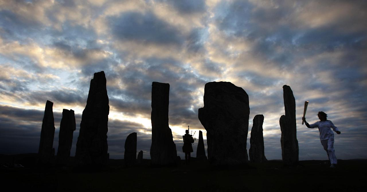 This image made available by LOCOG shows Kirsty Wade holding the Olympic Flame as a lone piper plays at the Calanais Standing Stones in Callanish on the Isle of Lewis, Scotland as the sun rises on Day 24 of the London 2012 Olympic Torch Relay, Monday, June 11, 2012. (AP Photo/Danny Lawson/LOCOG)