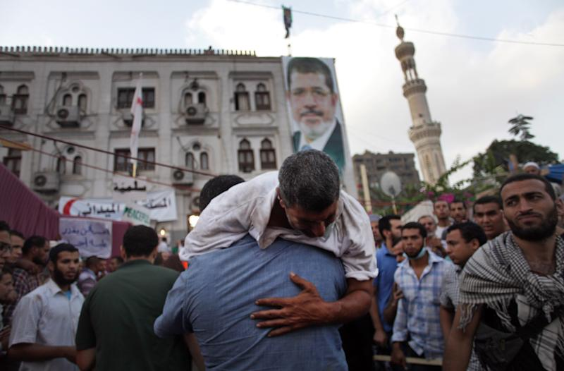 Supporters of Egypt's ousted President Mohammed Morsi carry an injured man to a field hospital following clashes with security forces at Nasr City, where pro-Morsi protesters have held a weeks-long sit-in, in Cairo, Egypt, Saturday, July 27, 2013. Police fired tear gas to disperse hundreds of Morsi supporters, setting off clashes that lasted for hours and left dozens of people dead. (AP Photo/Khalil Hamra)