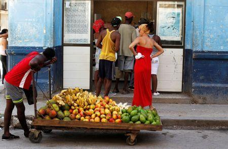 A man pushes a cart with fruits in front of a shop, as a picture of the former Cuban President Raul Castro is seen on the wall, in Havana, Cuba July 21, 2018. REUTERS/ Stringer