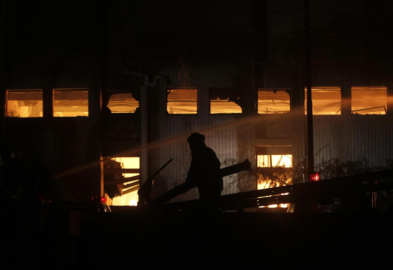 A fireman tries to extinguish a fire which broke out in a factory on Tuesday, Sept. 11, 2012 in Karachi, Pakistan. Factory fires in two of Pakistan's major cities killed 39 people and injured dozens more on Tuesday, including some who had to break through barred windows and leap to the ground to escape the flames. (AP Photo/Shakil Adil)