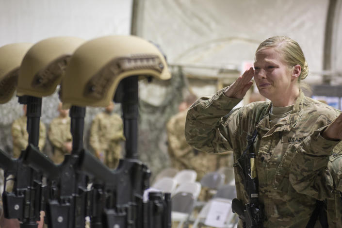 """FILE - In this Dec. 23, 2015 file photo, a U.S. service member salutes her fallen comrades during a memorial ceremony for six Airmen killed in a suicide attack, at Bagram Air Field, Afghanistan. ter 20 years America is ending its """"forever"""" war in Afghanistan. There's conflicting views even among U. S. military minds as to whether the time is right. For others there is another lingering question: Was it worth it? (Tech. Sgt. Robert Cloys/U.S. Air Force via AP)"""