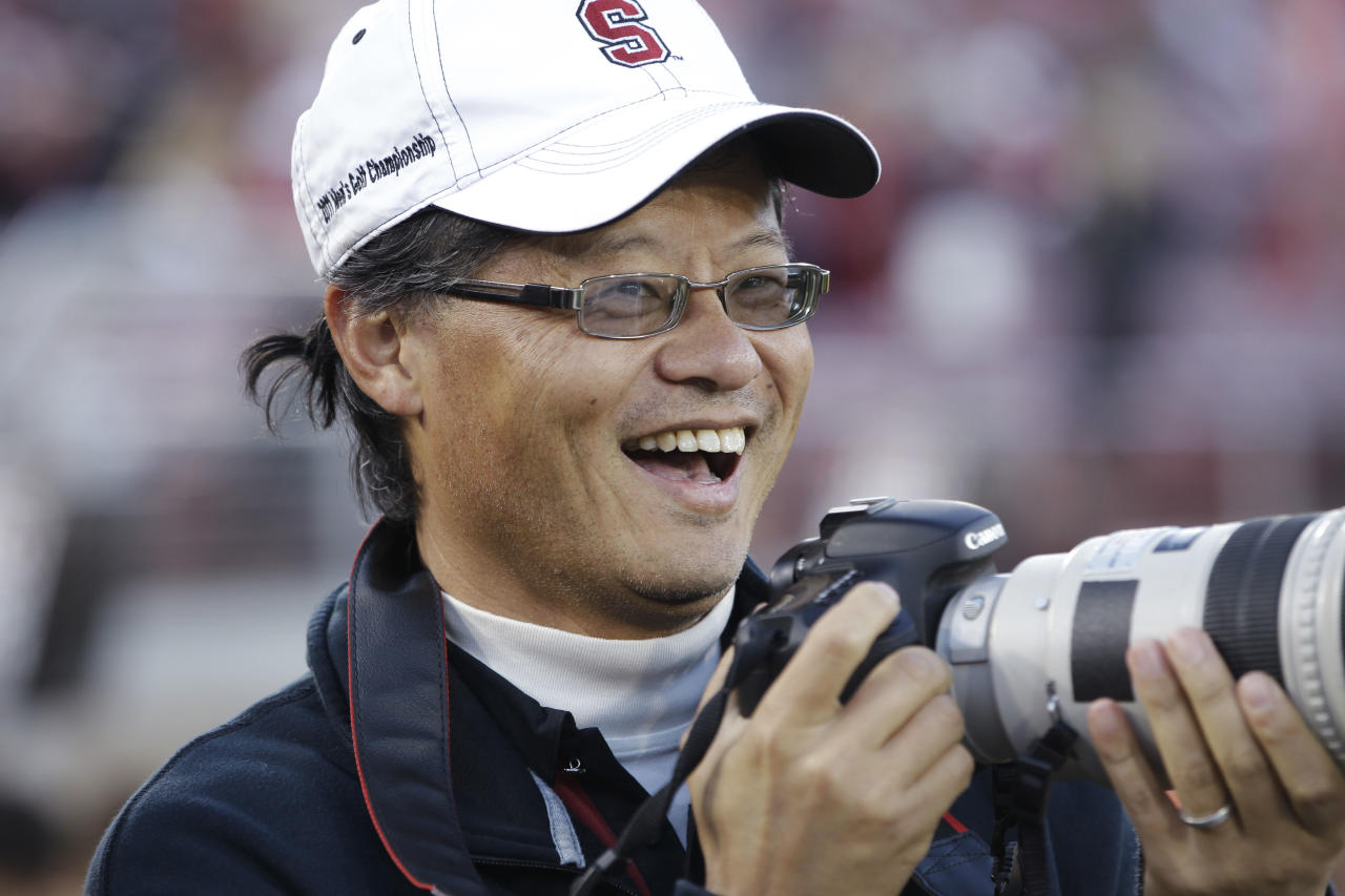 FILE - in this Nov. 26, 2011 file photo, Yahoo co-founder Jerry Yang takes pictures at an NCAA college football game in Stanford, Calif. Yang on Tuesday, Jan. 17, 2012 announced that he is leaving Yahoo. The surprise departure comes just two weeks after Yahoo Inc. hired former PayPal executive Scott Thomson as its CEO. (AP Photo/Paul Sakuma, File)