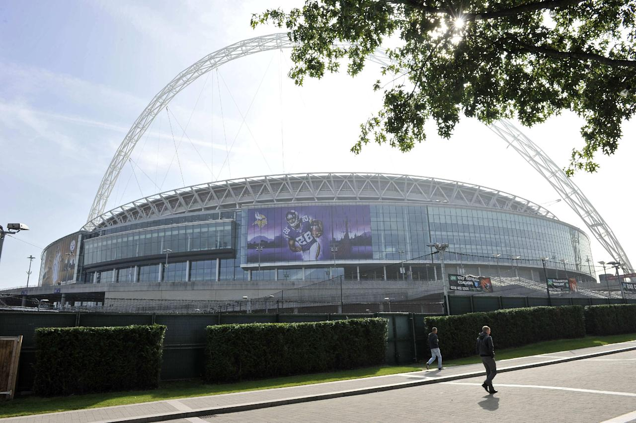 People walk past Wembley Stadium in London, Tuesday Sept. 24, 2013. The Pittsburgh Steelers are to play the Minnesota Vikings in the NFL International Series at Wembley Stadium in London on Sunday, Sept 29. (AP Photo/Sean Ryan, NFL)