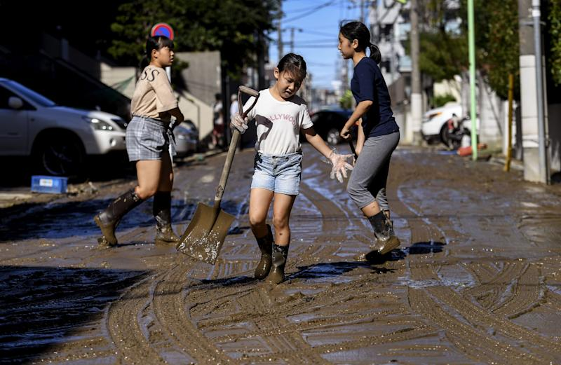 Children clear mud from a street after floodwaters receded in the aftermath of Typhoon Hagibis, in Kawasaki on Oct. 13, 2019. (Photo: William West/AFP via Getty Images)
