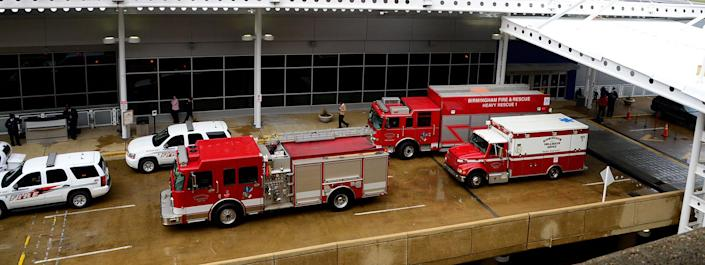 Fire trucks line up outside the terminal at the Birmingham-Shuttlesworth International Airport in Birmingham, Ala., where a message board sign fell on a family killing one child and injuring the mother and two other children Friday, March 22, 2013. (AP Photo/AL.com, Mark Almond) MAGS OUT