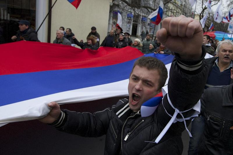 Local residents carry Russian flags and shout slogans rallying through the streets of Crimean capital Simferopol, Ukraine, on Saturday, March 1, 2014. Russian President Vladimir Putin asked parliament Saturday for permission to use the country's military in Ukraine, moving to formalize what Ukrainian officials described as an ongoing deployment of Russian military on the country's strategic region of Crimea. (AP Photo/Ivan Sekretarev)