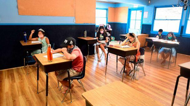 PHOTO: Children in an elementary school class wear masks and sit at desks spaced apart, per coronavirus guidelines, during summer school sessions at Happy Day School in Monterey Park, Calif., July 9, 2020. (Frederic J. Brown/AFP via Getty Images)