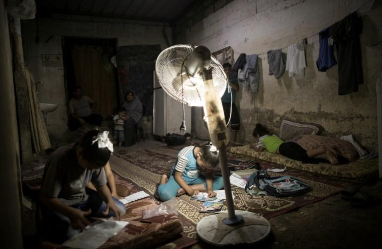 Palestinian children do their homework during a power cut in an impoverished area in Gaza City