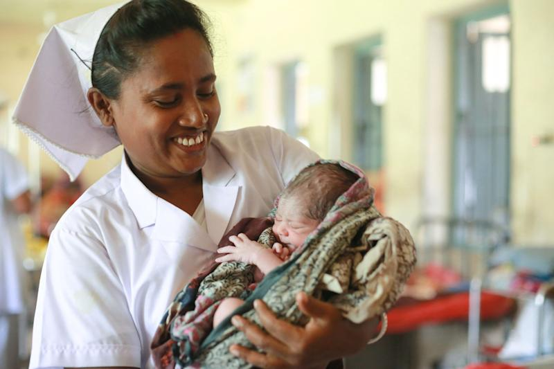 A midwife in <strong></strong>Bangladesh holds a 1-day-old baby.
