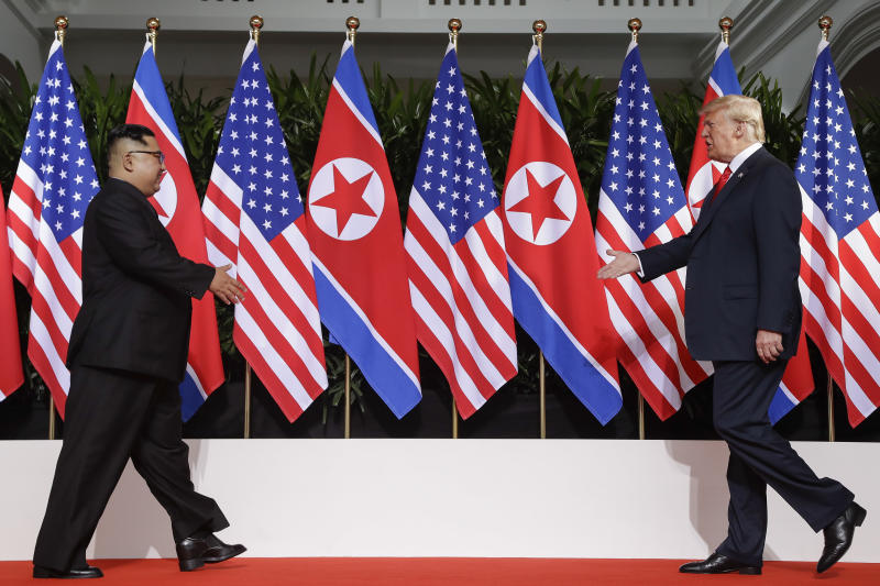 """FILE - In this June 12, 2018, file photo, U. S. President Donald Trump, right, and North Korea leader Kim Jong Un walk toward each other at the Capella resort on Sentosa Island in Singapore. North Korea says planned U.S.-South Korean military drills would amount to """"throwing a wet blanket over the spark"""" of nuclear negotiations between Pyongyang and Washington. (AP Photo/Evan Vucci, File)"""