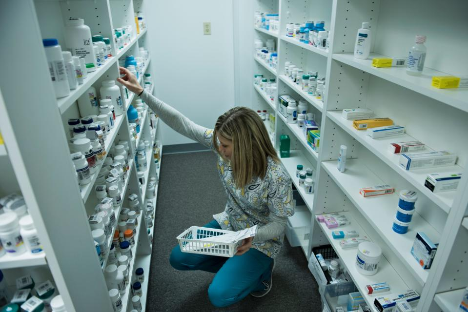 A staff member sorts through drugs drugs while filling a prescription. (Photo: BRENDAN SMIALOWSKI/AFP via Getty Images)