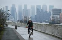 FILE PHOTO: FILE PHOTO: Buildings are seen in the Canary Wharf business district, as a man cycles along a path, amid the outbreak of the coronavirus disease (COVID-19), in London