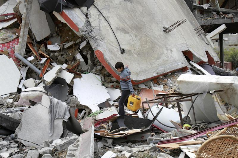A Palestinian boy walks through the rubble of a destroyed building following an Israeli air strike in Jabaliya, Monday, March 12, 2012. Israeli air strikes killed two Palestinian militants and a schoolboy in the Gaza Strip on Monday and Palestinian rocket squads barraged southern Israel, in escalating fighting that has defied international truce efforts. (AP Photo/Adel Hana)
