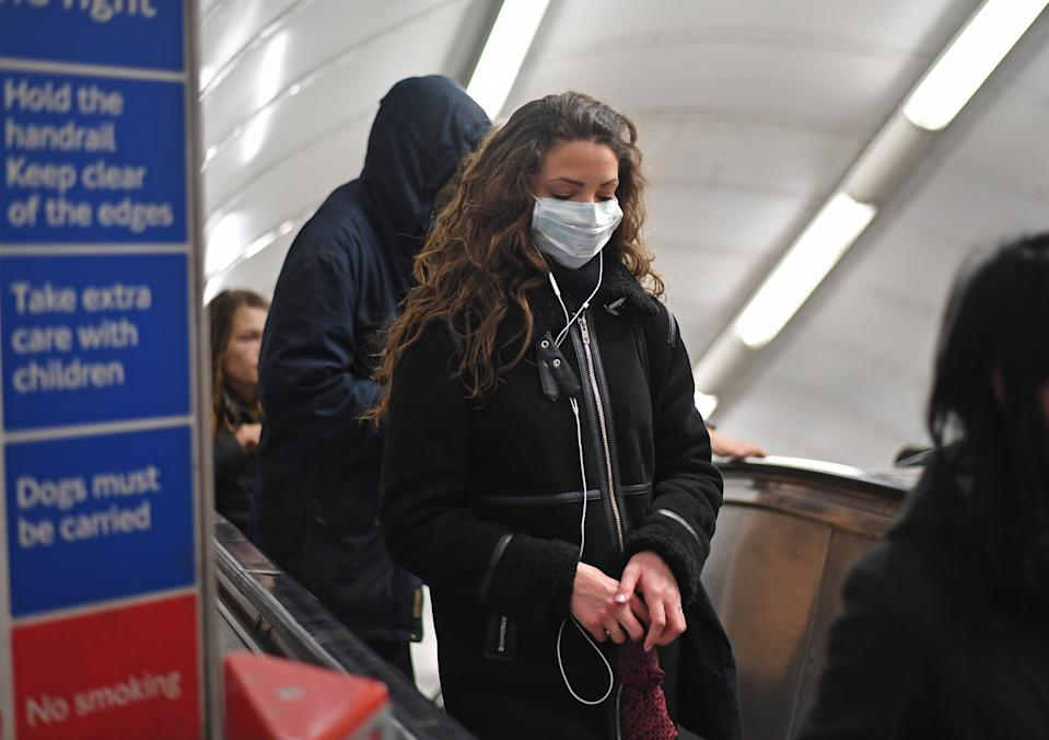 A woman at Green Park station on the London Underground tube network wearing a protective facemask.