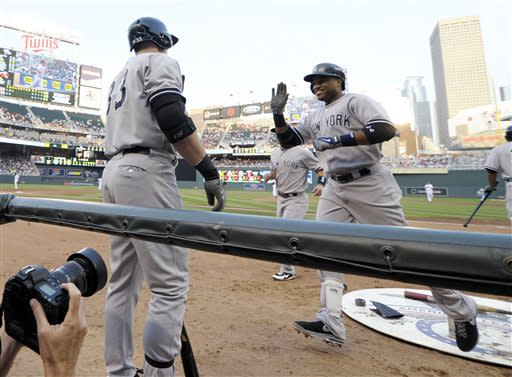 New York Yankees' Robinson Cano, right, is all smiles as he reaches the dugout after his second home run of the game in the third inning of a baseball game, Monday, July 1, 2013 in Minneapolis. (AP Photo/Jim Mone)
