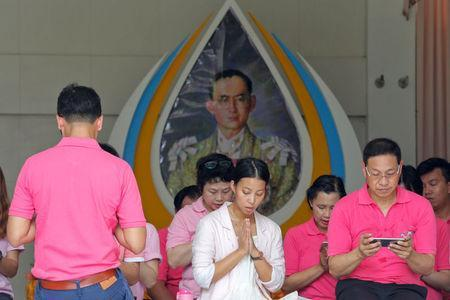 Well-wishers wear pink shirts as they pray in front of a picture of Thailand's King Bhumibol Adulyadej at Siriraj Hospital in Bangkok, Thailand, October 11, 2016. REUTERS/Chaiwat Subprasom