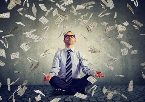 A man sits in a yoga pose as dollar bills fall down around him.