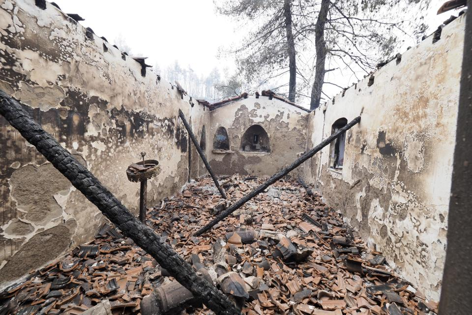 A burnt Greek Orthodox chapel during a wildfire in Kirinthos village on the island of Evia, about 135 kilometers (84 miles) north of Athens, Greece, Friday, Aug. 6, 2021. Thousands of people fled wildfires burning out of control in Greece and Turkey on Friday, including a major blaze just north of the Greek capital of Athens that claimed one life, as a protracted heat wave left forests tinder-dry and flames threatened populated areas and electricity installations. (AP Photo/Thodoris Nikolaou)
