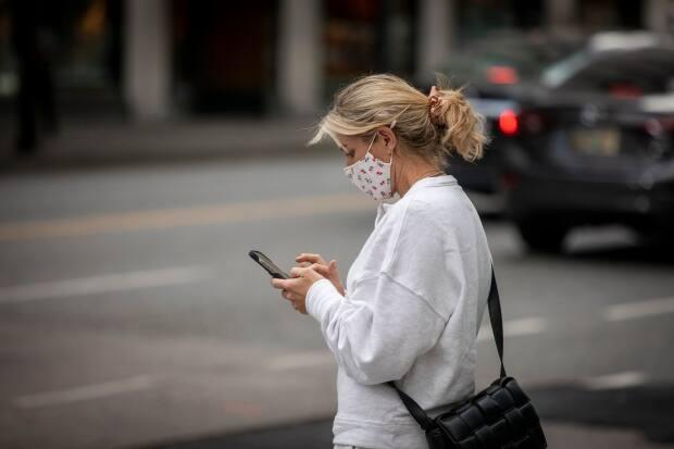A masked person checks their phone in downtown Vancouver on Oct. 4.  (Ben Nelms/CBC - image credit)