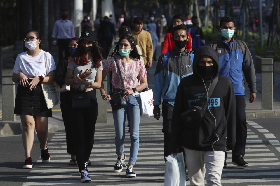 People wearing face masks as a precaution against the new coronavirus walk on a street in Jakarta, Indonesia, Tuesday, July 7, 2020. (AP Photo/Achmad Ibrahim)