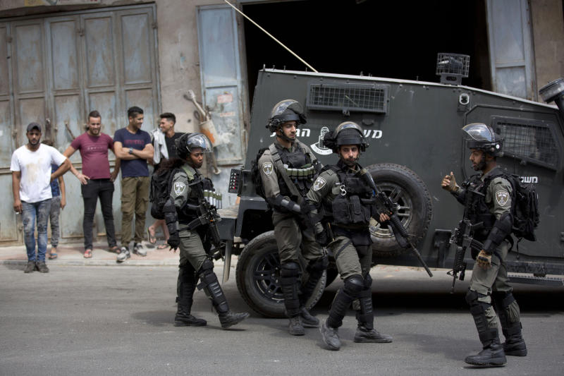Israeli border police officers, stand in the village of Azzun near the West Bank city of Qalqilya, Saturday, Sept. 7, 2019. An Israeli father and his son were stabbed near the town of Qalqilya. Israeli medical services said the 17-year-old son was in a serious condition. The military says it's examining the backgrounds of the incident. (AP Photo/Majdi Mohammed)
