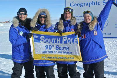 The Test Your Limits team gets a flag to mark their achievement of reaching the South Pole.
