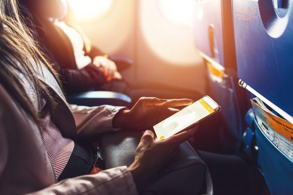 A woman using a tablet on an airplane