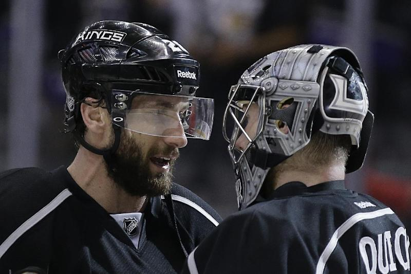 Los Angeles Kings center Jarret Stoll, left, celebrates their win against the Chicago Blackhawks with goalie Jonathan Quick during the third period of Game 4 of the Western Conference finals of the NHL hockey Stanley Cup playoffs in Los Angeles, Monday, May 26, 2014. The Kings won 5-2. (AP Photo/Chris Carlson)