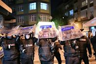 Turkish police take cover under their shields as protesters throw objects from their homes during the latest anti-government demonstration