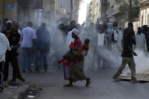 A woman carrying her baby runs past anti-government protestors during clashes with police in Dakar, Senegal, February 17, 2012.
