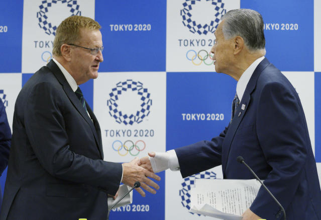 International Olympic Committee (IOC) Vice President John Coates, left, and Yoshiro Mori, president of the Tokyo Organizing Committee of the Olympic and Paralympic Games, shake hands after their joint press conference in Tokyo Tuesday, April 24, 2018. Coates, the head of an IOC inspection team, urged organizers of the 2020 Tokyo Olympics to be more direct answering questions about preparations with the Games opening in just over two years. The advice from Coates on Tuesday came a week after several sports federations openly criticized Tokyo's preparations. (AP Photo/Eugene Hoshiko)