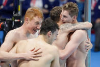 Britain's men's 4x200-meters relay team Tom Dean, James Guy, Matthew Richards and Duncan Scott celebrare after winning the gold medal at the 2020 Summer Olympics, Wednesday, July 28, 2021, in Tokyo, Japan.(AP Photo/Charlie Riedel)