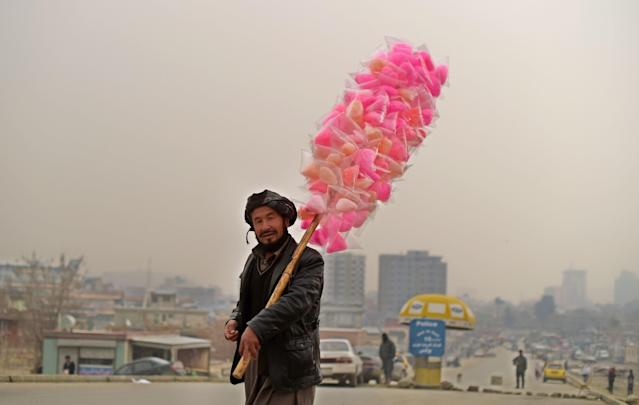 <p>An Afghan vendor sells candy floss as he walks on the streets of Kabul on January 5, 2017. (Photo: Shah Marai/ AFP/Getty Images) </p>