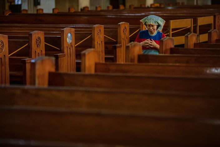 A woman prays on her knees in the aisle of an empty church as authorities ban religious gatherings amid the threat of the coronavirus on March 22, 2020 in Manila, Philippines.